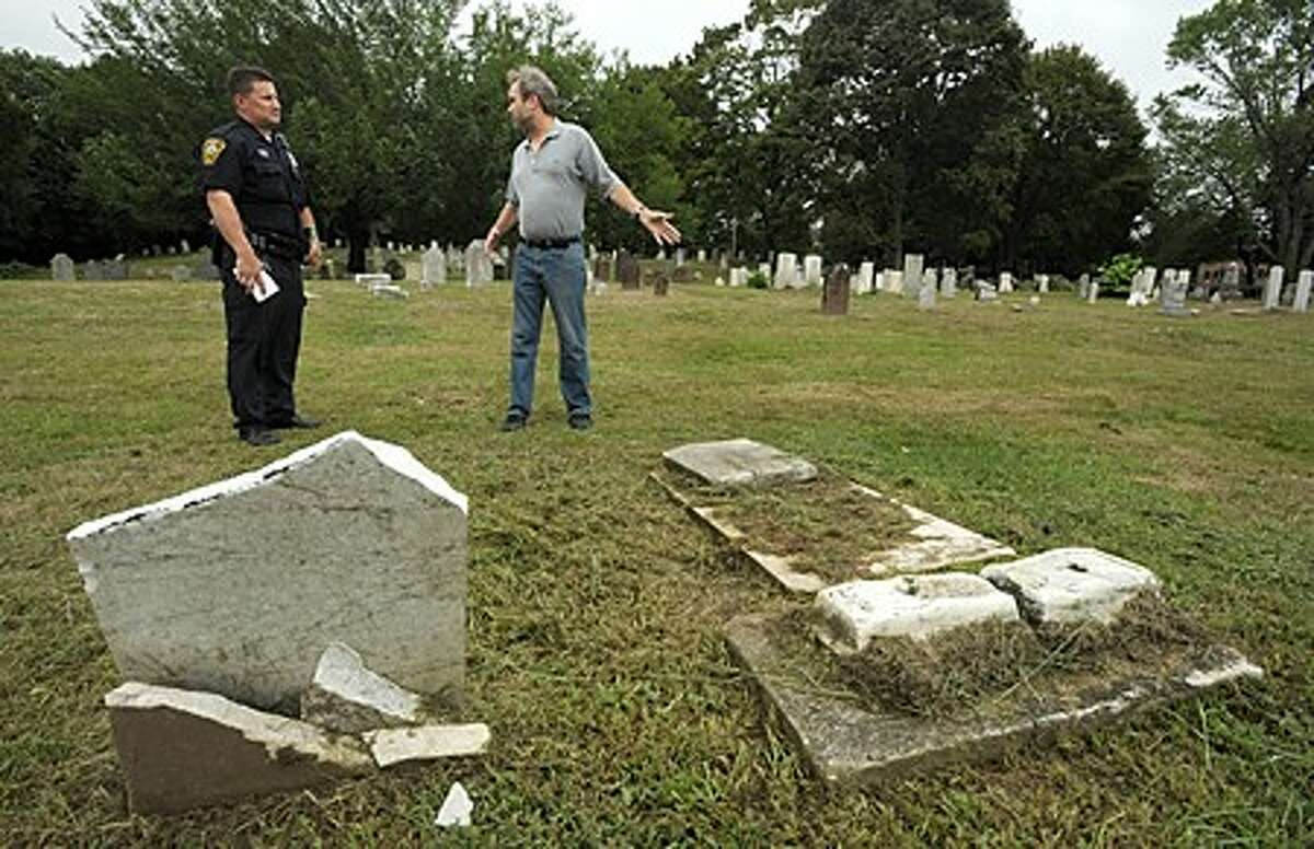 Norwalk Police officer Lou Proto and Chairman of the Norwalk Historical Commission, David Park, investigate more damaged headstones at the historic Pine Island Cemetary Wednesday morning. Vandalisim has occured at the cemetary several years before forcing the comission to install over $10,000 of security lighting at the historic site. Hour photo / Erik Trautmann Hour photo / Erik Trautmann