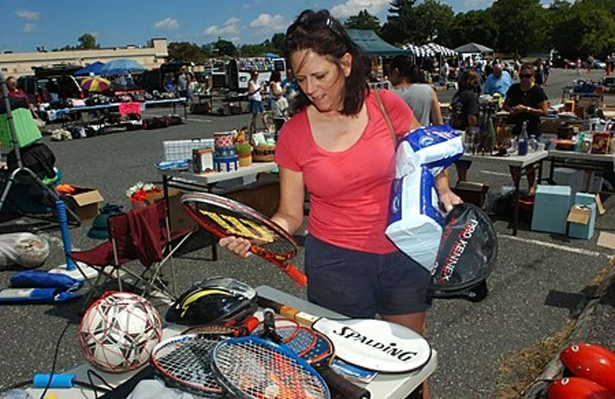 Michelle Markelon shops for tennis rackets at the Marching Bears Flea Market fundraiser Saturday at Andrews Field. Hour photo / Erik Trautmann