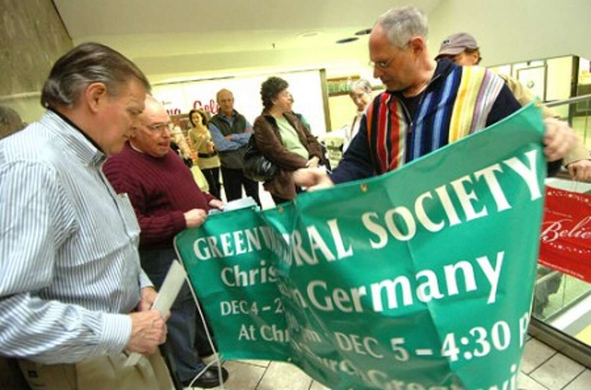 Photo/Alex von Kleydorff. Mark Guttenberg with the Greenwich Chorale Society prepares the banner for a singing entrance ino the atrium at Stamford Town Center.