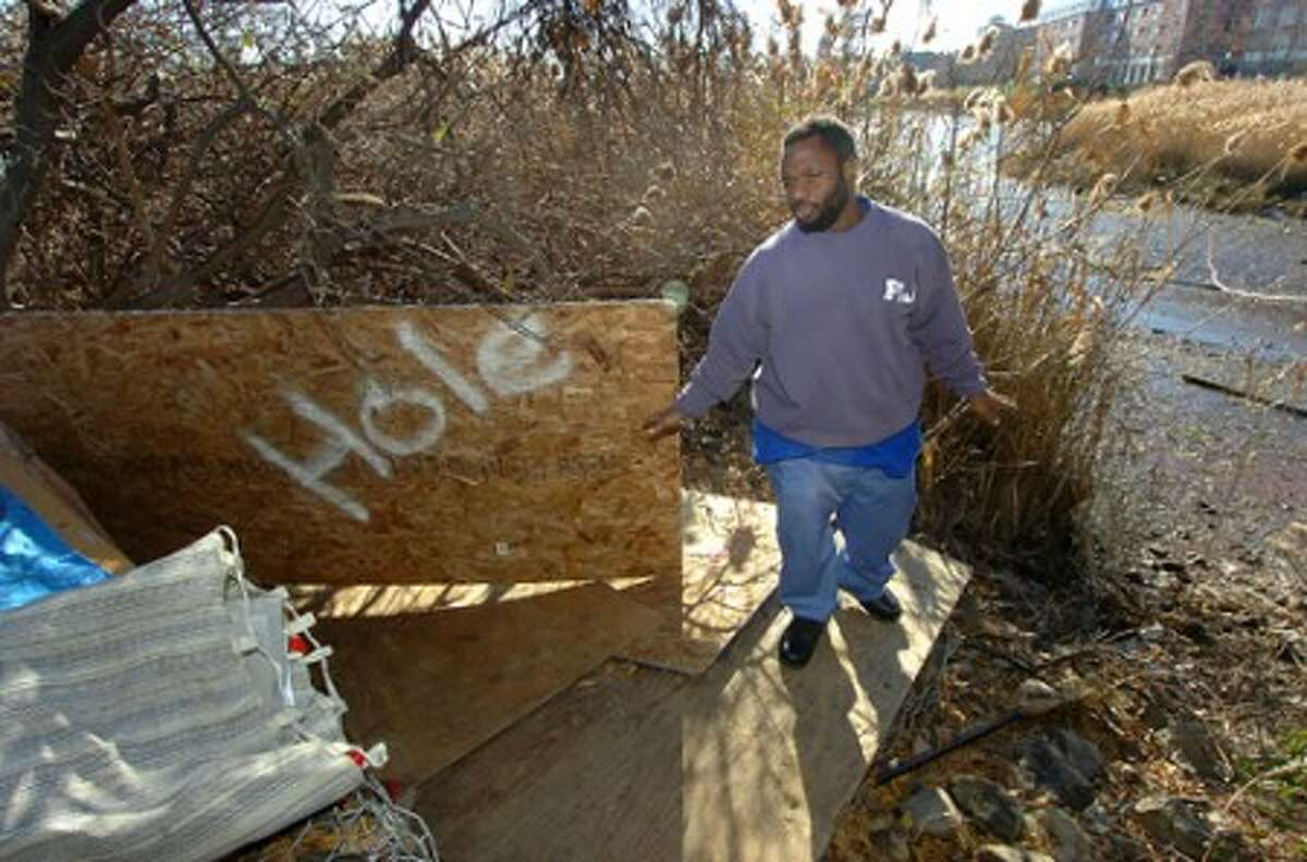 Photo/Alex von Kleydorff. With Luxury condos across the Norwalk River, Tyler Anderson starts to clear out his shelter in Oyster Shell park.