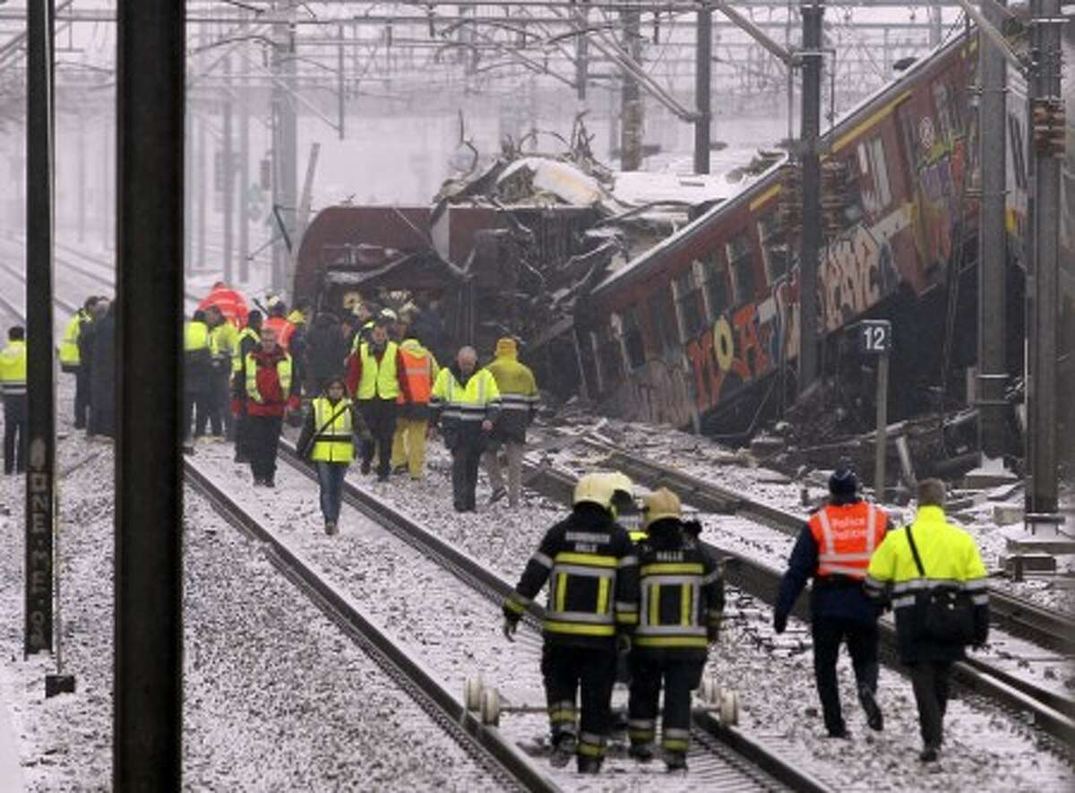 Rescue workers walk along the wreckage of two commuter trains in Buizingen, Belgium Monday, Feb. 15, 2010. Two commuter trains collided head-on at rush hour in a Brussels suburb Monday, killing 20 people, Belgian officials said. (AP Photo/Yves Logghe)