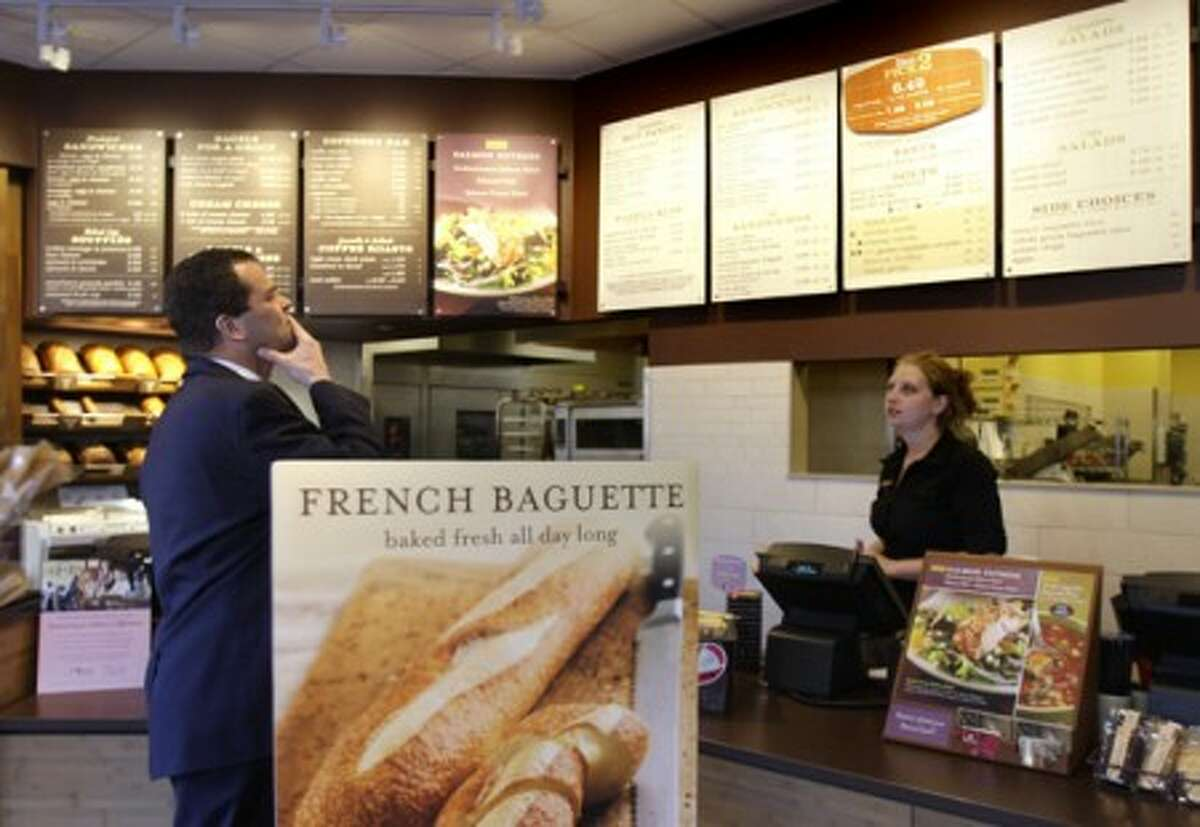 A customer reviews the sandwich board at the Panera store in Brookline, Mass. Panera bread company is announcing that they will become the first chain to post calories on menus nationally. (AP Photo/Charles Krupa, File)