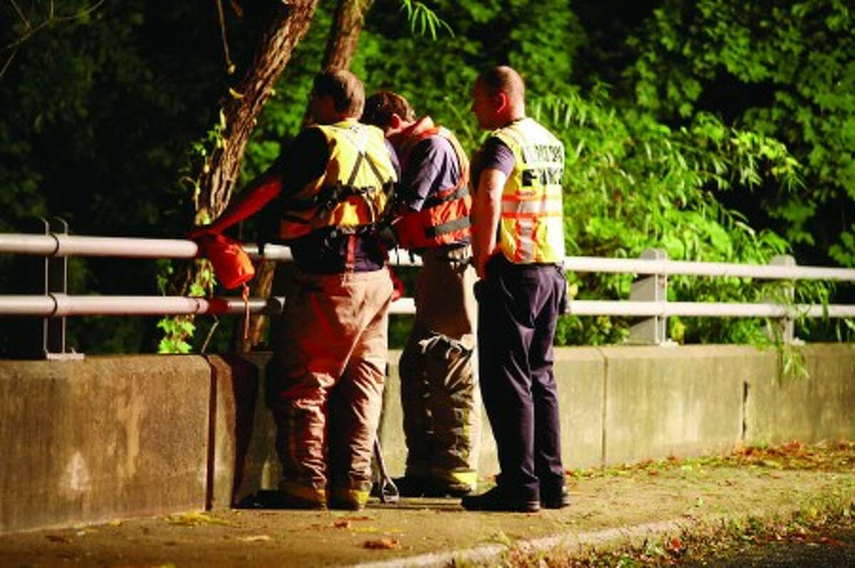 Search and Rescue workers look for a body that drowned in the Norwalk River on Cannon Road in Wilton Friday evening. Hour Photo / Danielle Robinson