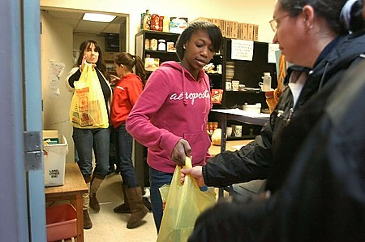 Kafesha Thomas, 17, and her family, The Borrero''s, volunteer together for the first time at the Christian Community Action food pantry Saturday. Hour photo / Erik Trautmann