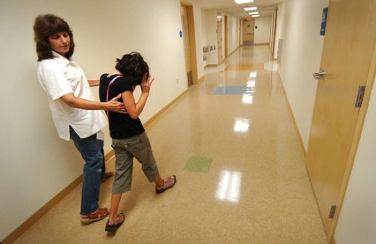 Photo/Alex von Kleydorff. Senior Instructional Assistant Pam Skudlarek walks with Jaya Dominici trough a hallway back to one of the trainning rooms after some time in the playground at The Connecticut Center for Child development in Milford.