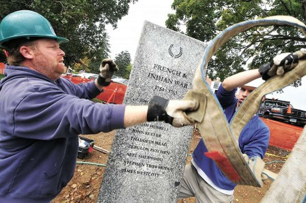 File photo/Alex von Kleydorff. l-R Troy Gerow and Ben Rehmeyer with Freshwater Stone move one of the stone columns for the Veterans Memorial Green to its final spot.