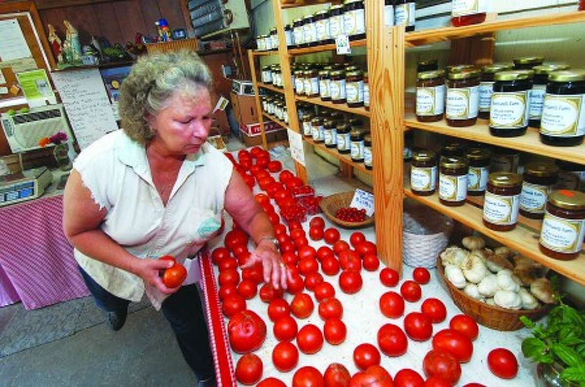 Photo/Alex von Kleydorff. Donna places tomatoes on a shelf under the jellies and preserves at Bucciarelli Farm in Norwalk
