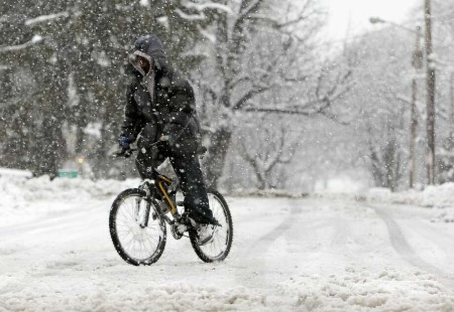 Tony Cordero of Albany bikes in the snow in Albany, N.Y., on Wednesday, Feb. 24, 2010. The first in a double-whammy storm has dumped more than a foot of wet, heavy snow on parts of eastern New York, closing hundreds of schools and knocking out power to more than 100,000 customers. (AP Photo/Mike Groll)