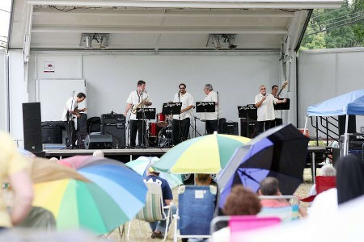 A crowd full of umbrellas listens to a performance by Deja Vu on the Norwalk Town Green Sunday afternoon. Hour Photo / Danielle Robinson
