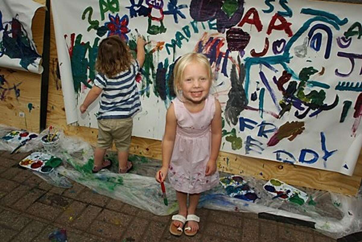 Ava Salvati, 3, and Morgan Tobin, 2, paint on a wall sponsored by Crabtree Toyota at the Sono Arts Festival Saturday. Hour photo / Erik Trautmann