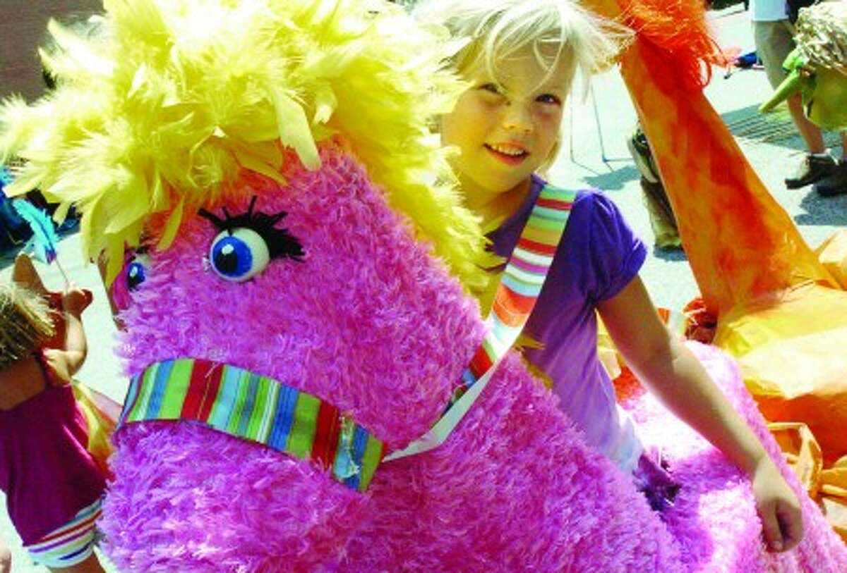 Ella Williams 6, at the SONO Arts Festival puppet parade marches down Washingtopn Street on Sunday. hour photo/matthew vinci