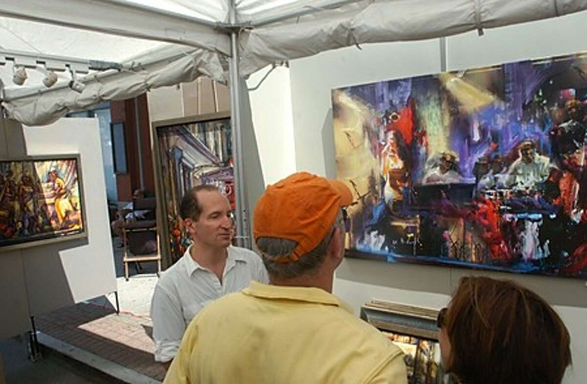 Allen Brown and Sue Taylor of Norwalk chat with artist Stuart Yankell, right, at the Sono Arts Festival Saturday. Hour photo / Erik Trautmann