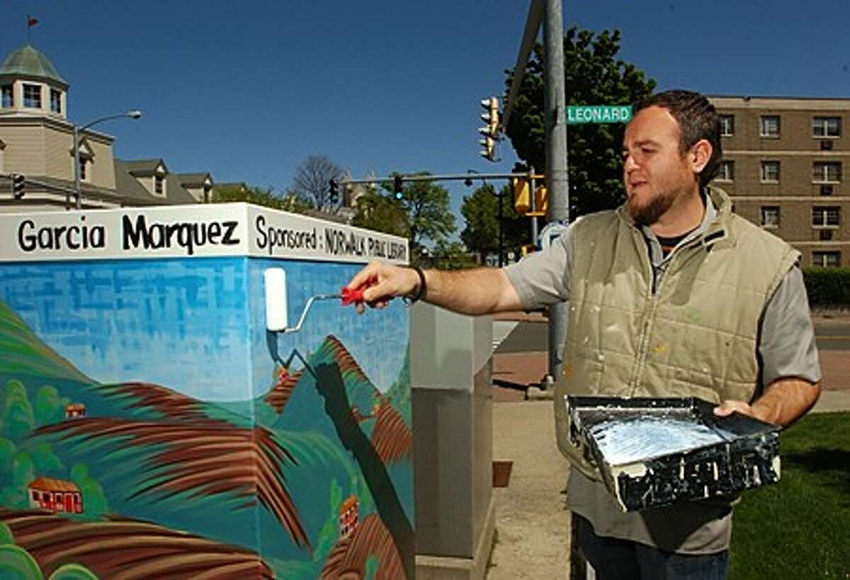 """The Norwalk Arts Commission has hired local artists to paint the gray electrical boxes in Norwalk to the theme of their favorite books. Painter Duvian Montoya ''s box is at the corner of West Ave and Leonard Street and is inspired by """"100 Years of Solitude"""" by Gabriel Garcia Marquez. Hour photo / Erik Trautmann"""
