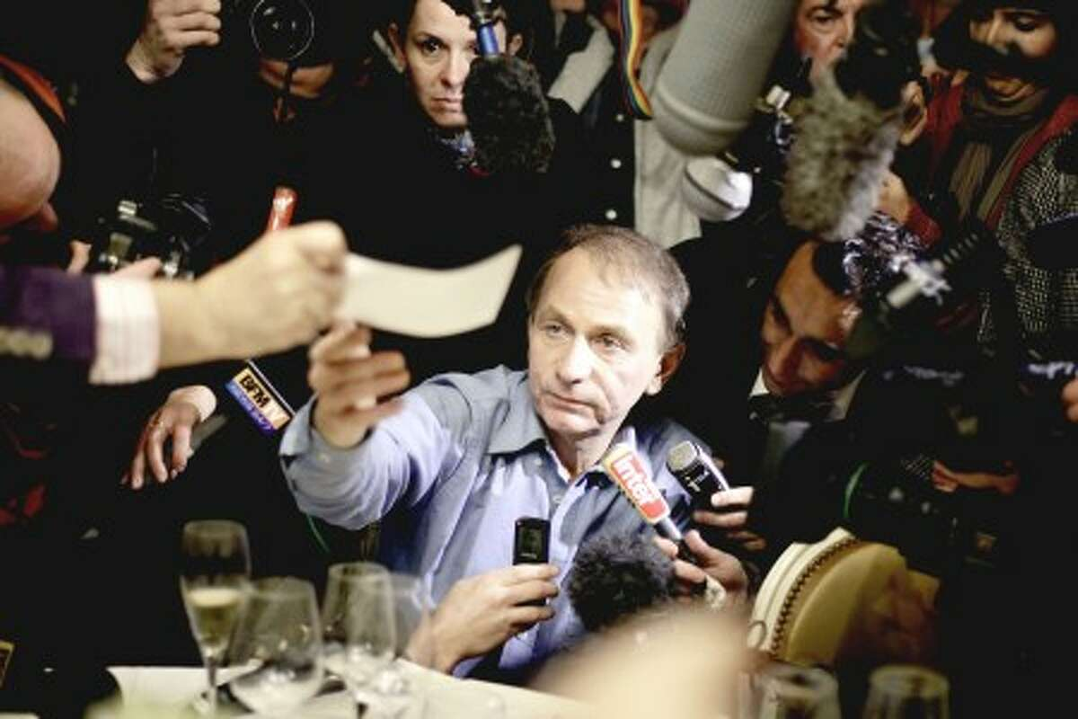 """Novelist Michel Houellebecq receives his check of ten euros (14 dollars) after he won the France''s top literary prize, the Goncourt, with his book """"La carte et le territoire,"""" or """"The map and the territory """", in Paris, Monday, Nov. 8, 2010. The novel tells of a solitary, misanthropic artist who becomes a critical darling and commercial success almost in spite of himself. (AP Photo/Thibault Camus)"""