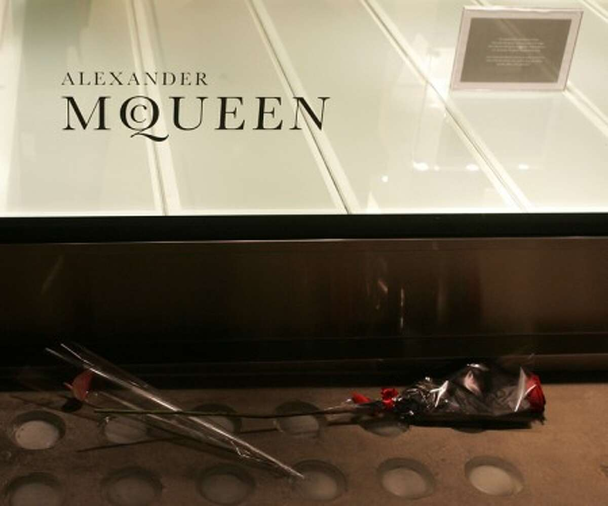 Flowers are seen under a logo of British fashion designer Alexander McQueen and a note informing customers of his death at his shop in central London, Thursday, Feb. 11. (AP Photo/Akira Suemori)