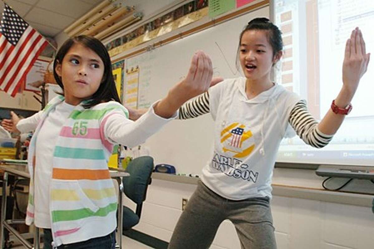 Amy Ochoa and her Kendall Elementary School 5th grade class learn Tai Chi from Stella Ruan, a graduate student from the University of Bridgeport, during a visit to the school Tuesday by 20 graduate students for a Chinese language immersion program. Hour photo / Erik Trautmann
