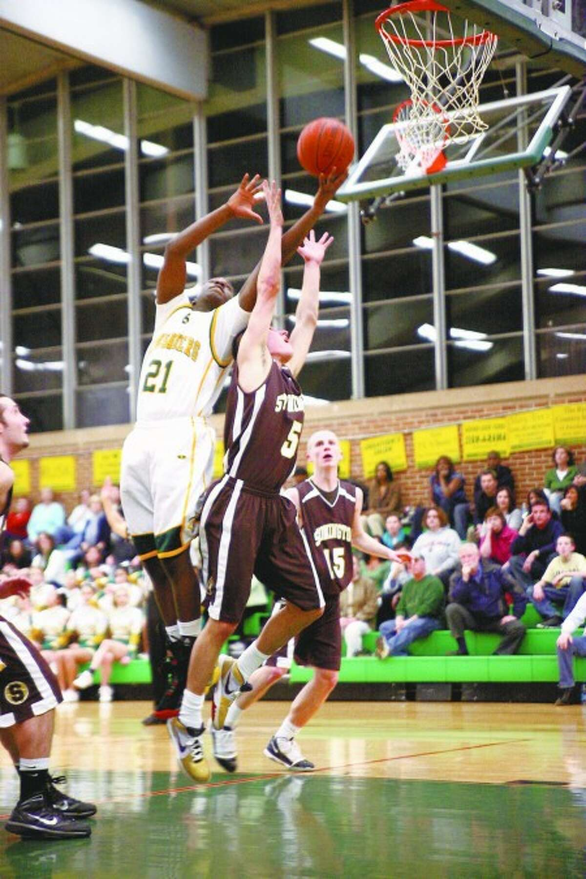Trinity Catholic''s Aaron Spence (21) has his hands on a rebound during a Class M state playoff game on Tuesday, March 9 at Walsh Court. Times photo/Danielle Robinson