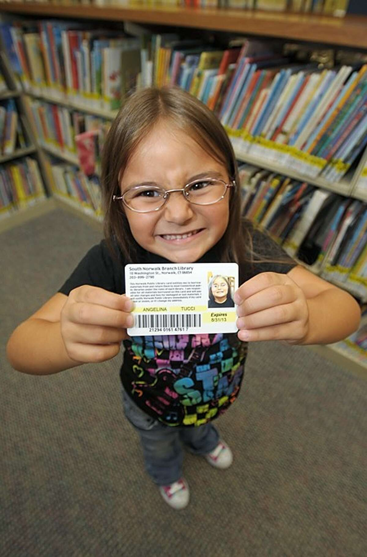5 year old Angelina Tucci shows off her first library card she recieved at the Norwalk Public Library''s main branch Wednesday. The Norwalk Public Schools in comjuction with the library look to issue a library card for every student in the school system. Hour photo / Erik Trautmann