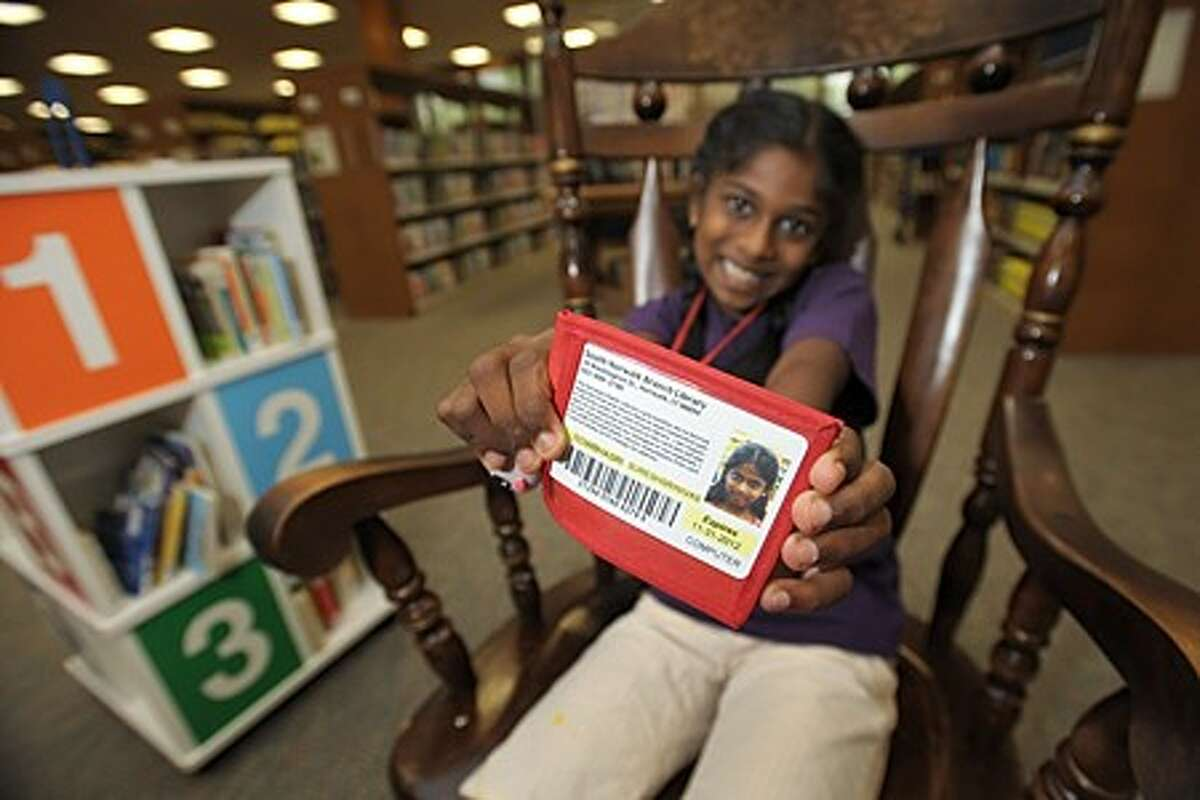8 year old Sowbharsri Sureshsrinivas shows off her library card and holder at the Norwalk Public Library''s main branch Wednesday. The Norwalk Public Schools in conjuction with the library look to issue a library card for every student in the school system. Hour photo / Erik Trautmann