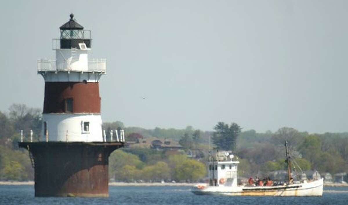 An oysterboat works the waters of Long Island Sound near Peck''s Ledge Lighthouse. Photo by CHRIS BOSAK