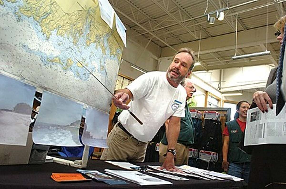 David Park, avid kayaker and member of the Norwalk River Watershed Association gives kayaking tips and sells his book Kayaking in and around the Norwalk Islands at the grand opening of REI on Friday. hour photo/matthew vinci