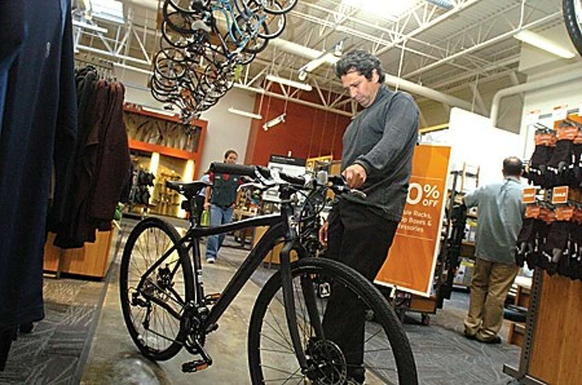 Fernando Lopez picks out a bike at the grand opening of REI on Connecticut Avenue Friday. He traveled up from Manhattan because this was the closest location of the store. hour photo/matthew vinci