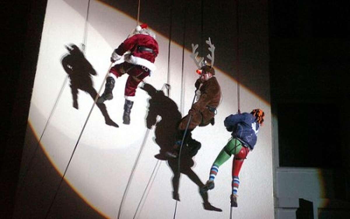 Photo/Alex von Kleydorff. Santa, Rudolf and the Elf, Brian Cashman repel down the Landmark building