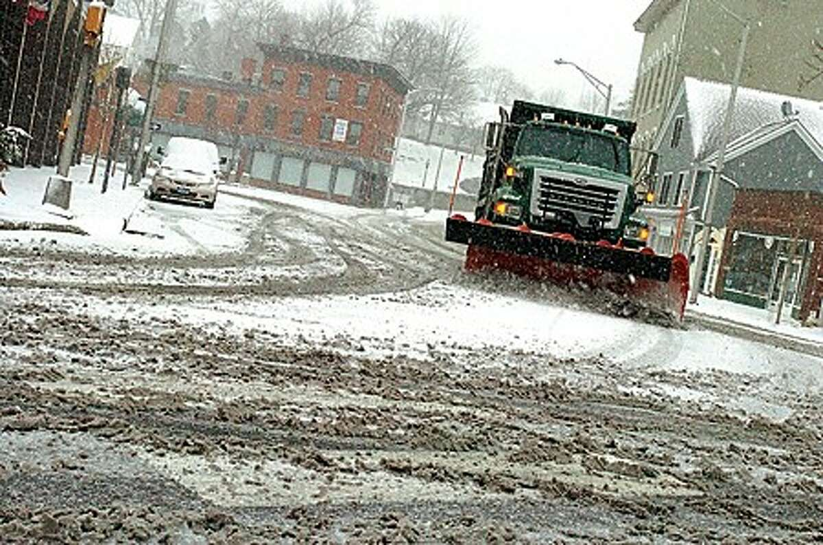 Snowplows work the streets of Norwalk Sunday afternoon in the first big snowstorm of the season. hour photo/matthew vinci