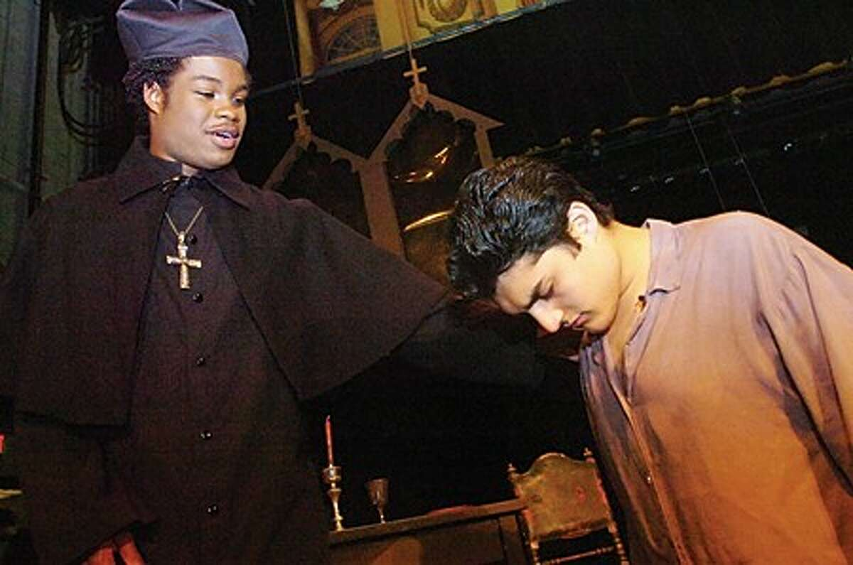 Travis White performs as the priest and John Cunsolo as Jean ValJean in the Norwalk High School dress rehearsal of Les Mis
