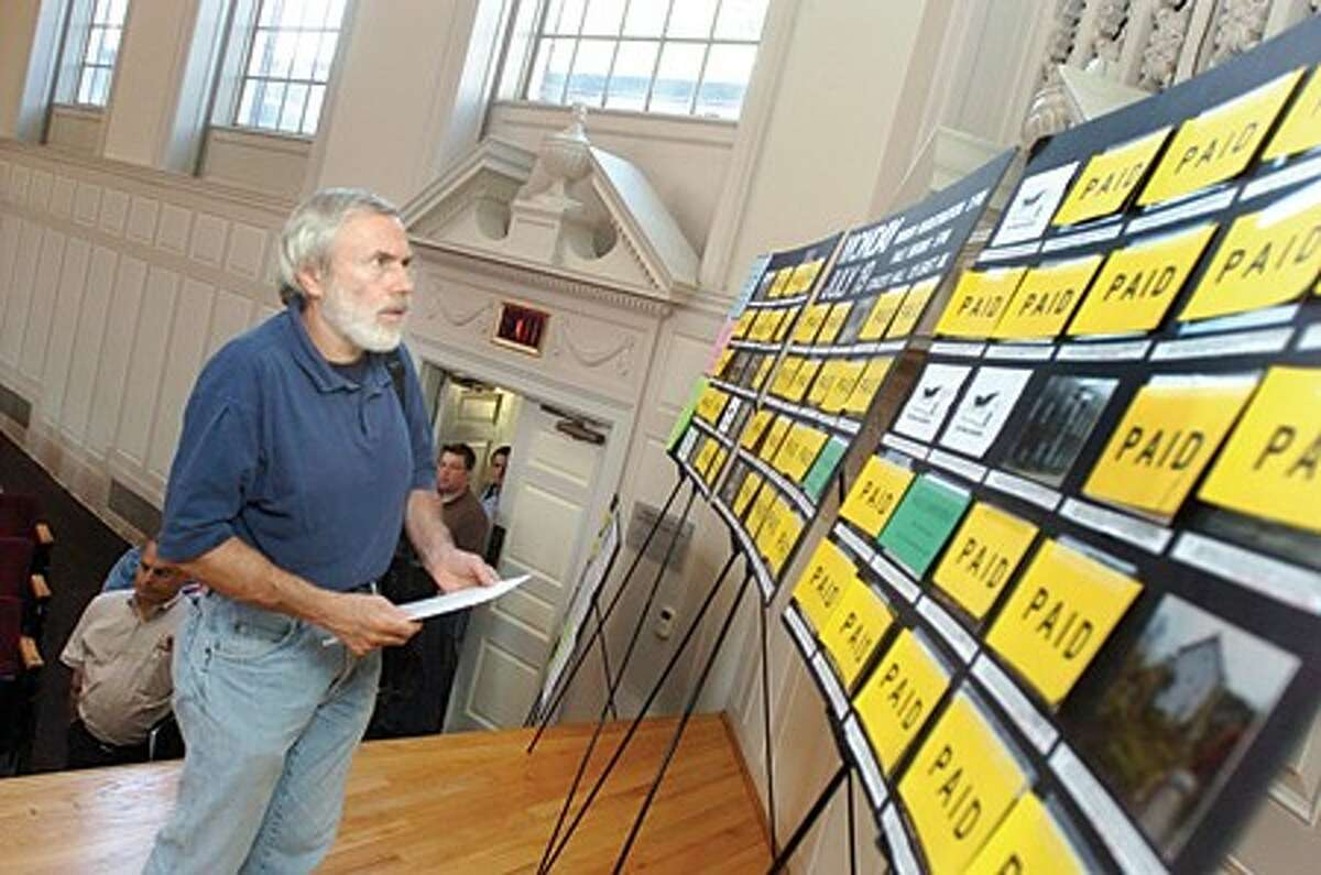 Carl Lupinacci looks over the sales of real estate properties that are delinquent at the Norwalk City Hall auditorium Monday. hour photo/matthew vinci