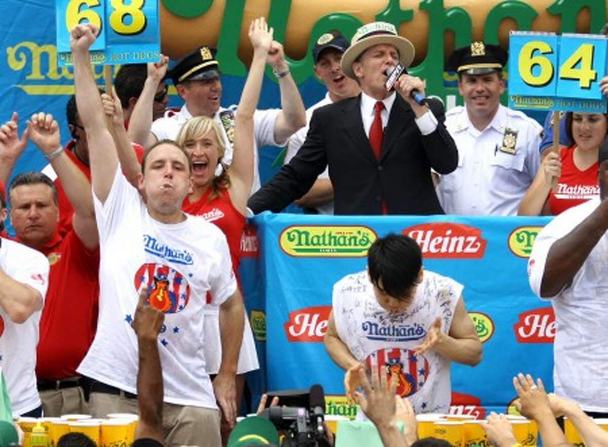 File - In this July 4, 2009 file photo, Joey Chestnut, left, of San Jose, Calif., defending champion of the Nathan''s Famous July 4th Hot Dog Eating Contest, celebrates his victory, logging his third consecutive win with a world-record 68 franks over former champion Takeru Kobayashi of Nagano, Japan, in New York. Kobayash, who won the contest for six years up to 2007, wants to compete in this weekend''s annual contest on Coney Island, but still can''t agree to a contract with the organizers, according to a report by Japan''s Kyodo news agency from New York on Friday, July 2, 2010. (AP Photo/Craig Ruttle, File)