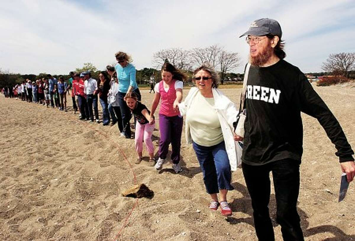 Human Tideline Committee member David Bedell leads 50 Stamford residents in the Tideline at Cove Island Park Saturday, marking the projected tide line if climate change is not reversed. The Human Tide Line Project as part of Soundwaters Earth Day celebration . Hour photo / Erik Trautmann