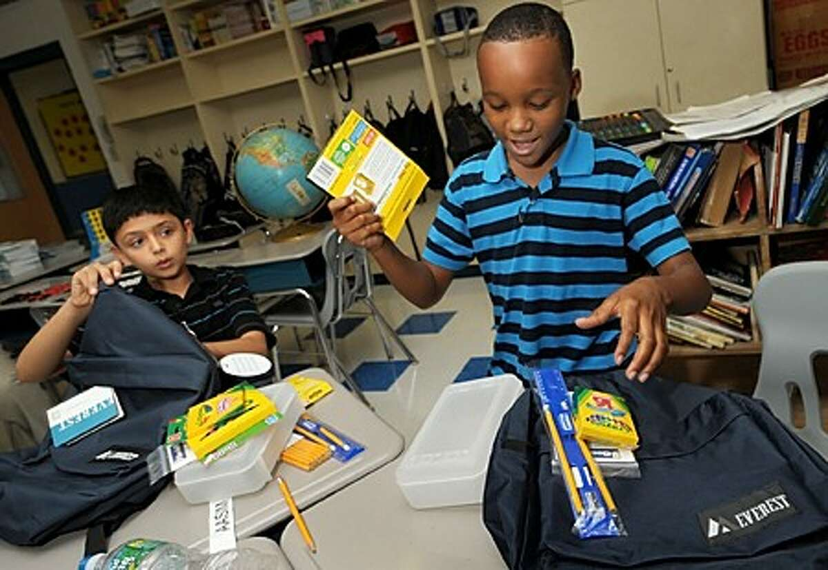 Kendall Elemenatry School 5th grader Darius Williams and Aasim Vhora look through the free backpacks and supplies they and the rest of their schoolmates recieved from Goodwill Friday afternoon. Goodwill donated over 2500 backpacks Friday to 5 different needy schools throughout Connnecticut. Hour photo / Erik Trautmann