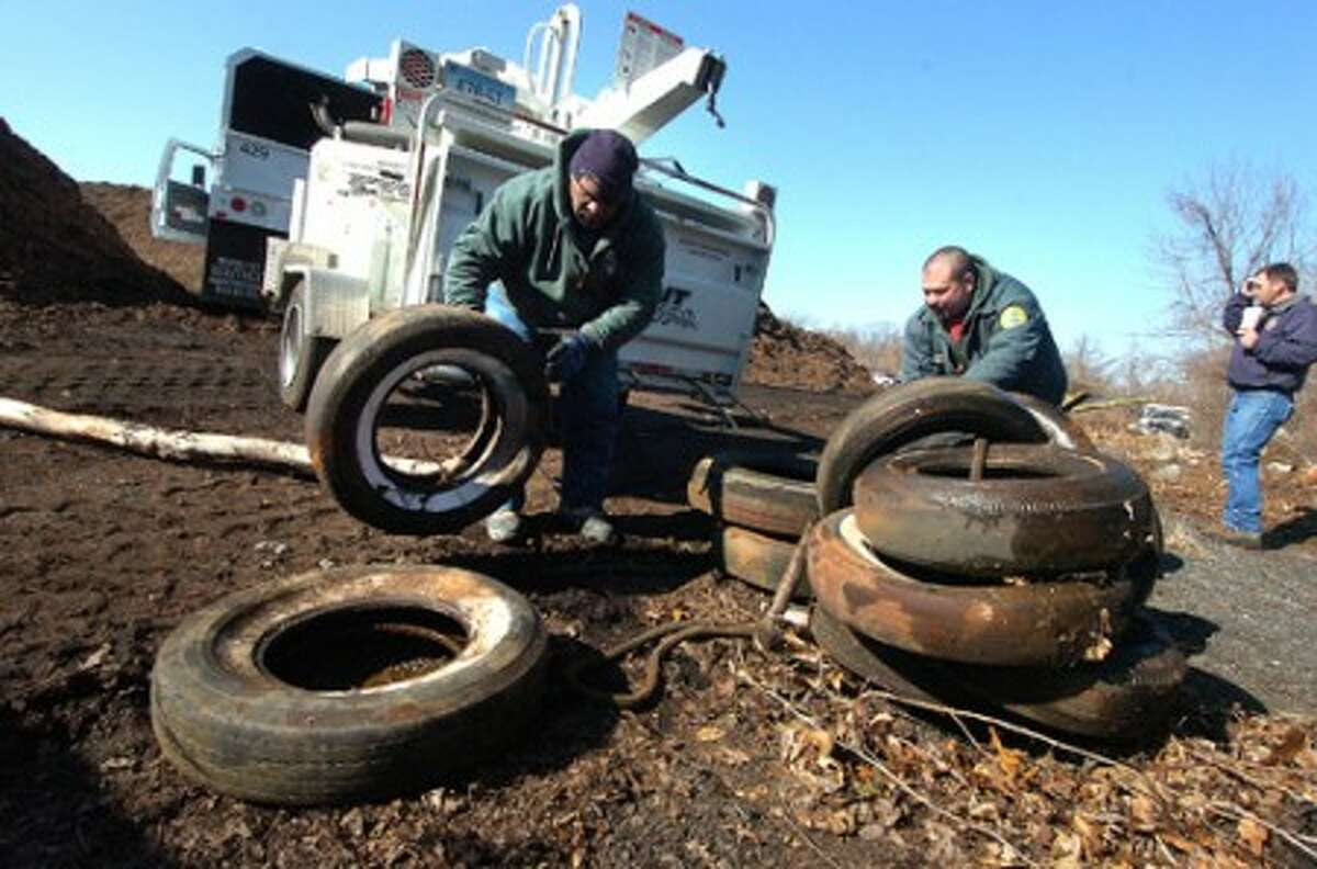 Photo/Alex von Kleydorff. l-R Pete Williams and Rocky Romanos with the city''s parks department un tangle some car tires for loading in a truck after they were pulled by a winch from a stream down a hill at the former Scofield Town Dump site.