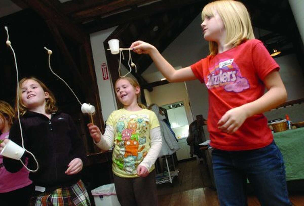 Nine year olds, Quincy Cole, Nicole Case and Emme Cropper test out their cup and ball toys they made at the Kids Day event held at the Wilton Historical Society on Monday/photo matthew vinci