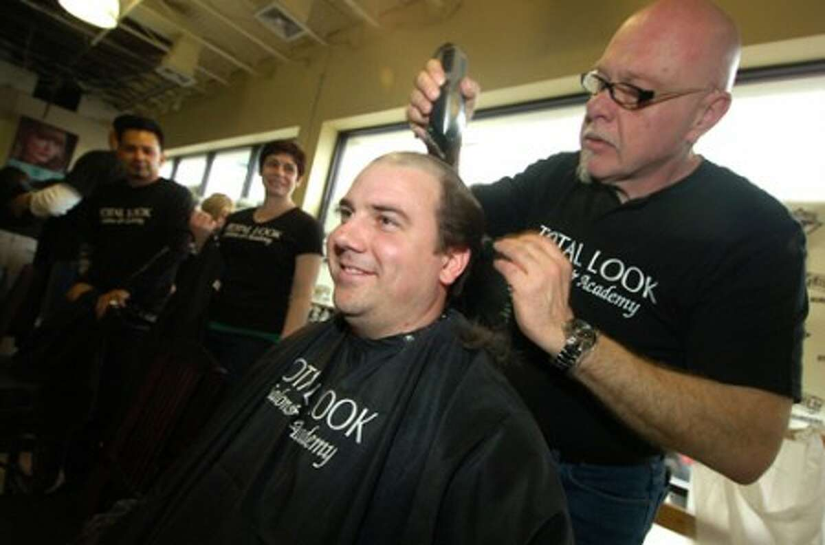 Photo/Alex von Kleydorff. Wilton Police officer David Hartman has his head shaved for Cancer research for children during St Baldricks in Fairfield last year. Officer hartman has already shaved his head at the Arena at Harbor Yard for this year''s event.