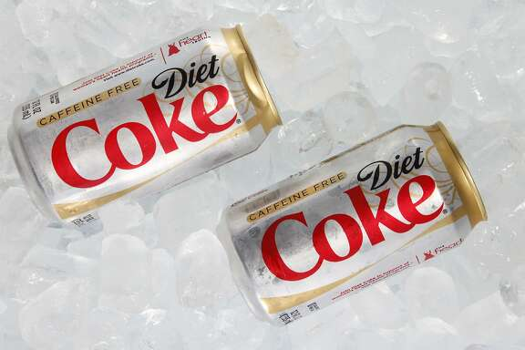 "FILE - This Monday, Oct. 15, 2012 file photo shows two cans of Caffeine Free Diet Coke on ice in Surfside, Fla. During a conference call with analysts Tuesday, Oct. 15, 2013, a Coca-Cola executive noted that Diet Coke was ""under a bit of pressure"" because of people's concerns over its ingredients, alluding to the growing wariness of artificial sweeteners in recent years. Soda has been under fire from health advocates for several years now, and Americans have been cutting back on sugary fizz for some time. But in a somewhat newer development, diet sodas are falling at a faster rate than regular sodas, according to Beverage Digest, an industry tracker. (AP Photo/Wilfredo Lee, File)"