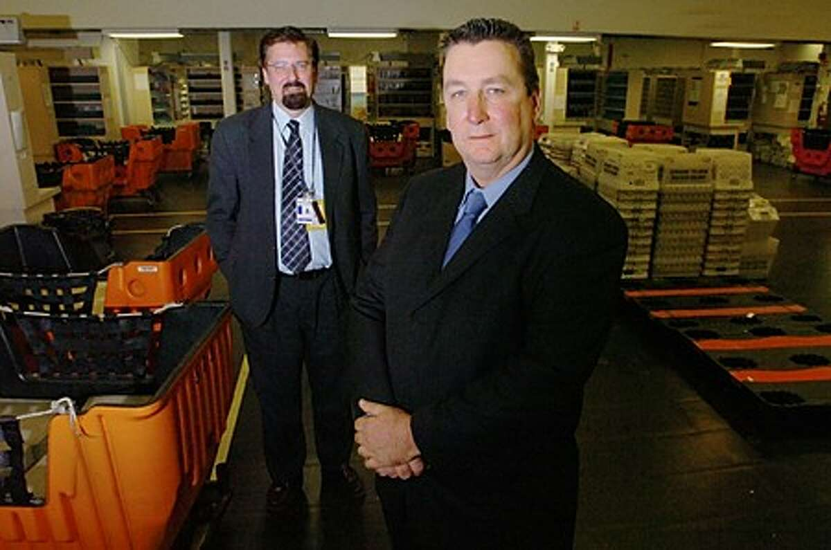 Stamford Postmaster Mark Dolan, right, who is retiring after 32 years, and interim Postmaster, Marcel Paquette at the Camp St Post Office in Stamford. Hour photo / Erik Trautmann