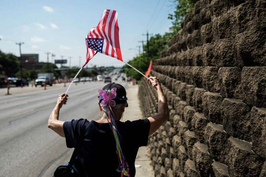 San Antonio, Texas -- June 17, 2016 -- Mary Elizabeth Gephart Bruton waved flags as she walked to gathering of people supporting Republican presidential candidate Donald Trump's visit to San Antonio near his private fundraiser at Oak Hills Country Club. Ray Whitehouse/for the San Antonio Express-News