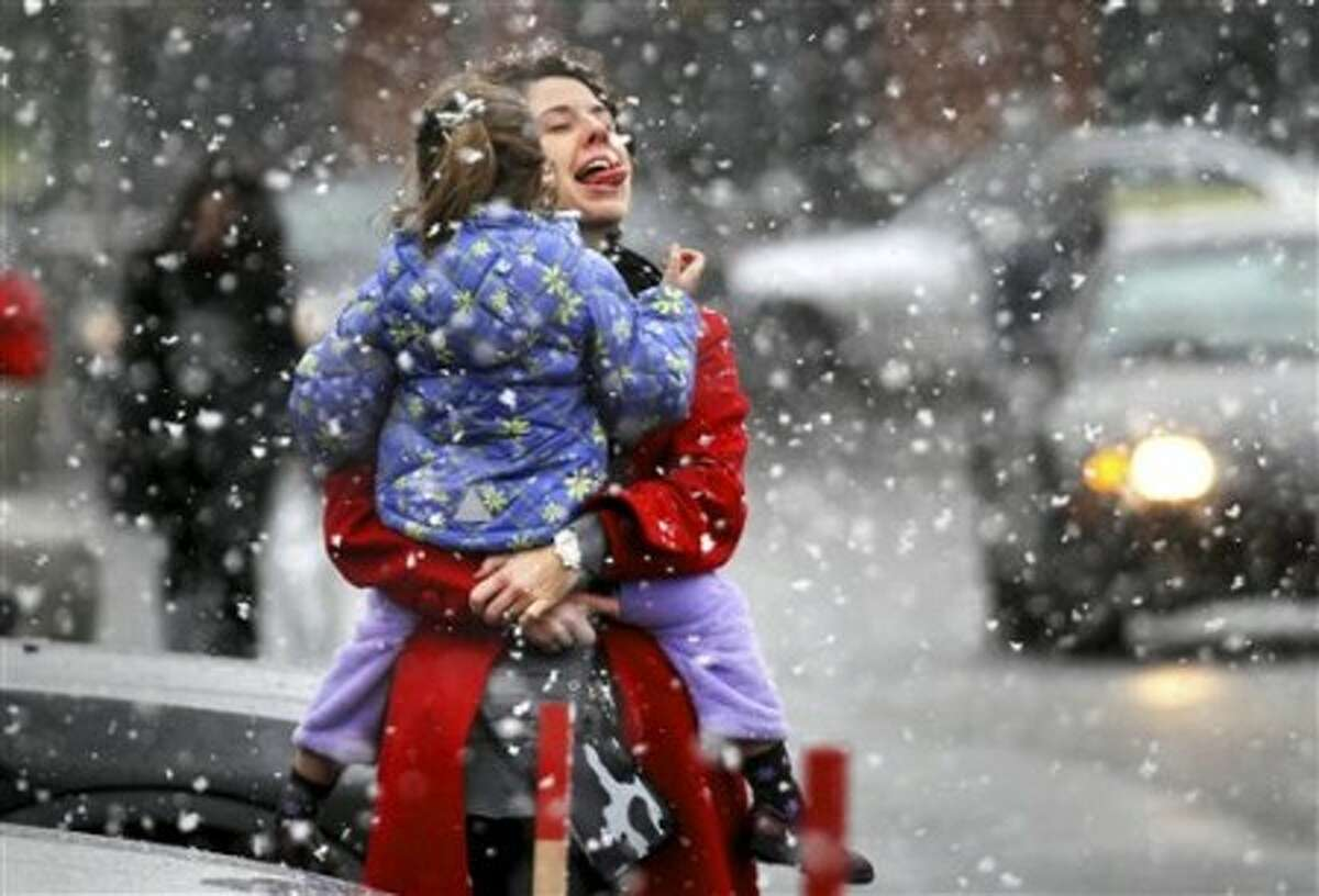 In this Dec. 22, 2010 photo, Maura Webster of Marlborough, Mass., tries to catch a snowflake on her tongue while carrying her daughter Emma, 4, after Christmas shopping at Shopper''s World in Framingham, Mass. (AP photo/The Boston Globe/Bill Greene) MANDATORY CREDIT; BOSTON HERALD OUT; QUINCY OUT; MAGS OUT; INTERNET OUT; NO SALES.
