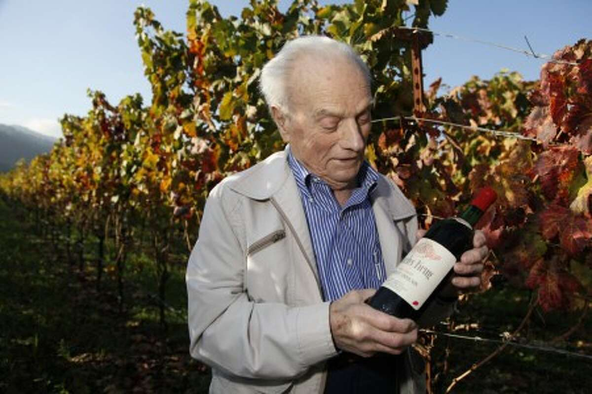 This photo taken Nov. 4, 2009 shows Peter Mondavi Sr. looking at a bottle of 1944 Charles Krug Cabernet Sauvignon, the first his family produced, while standing in a vineyard at the winery in St. Helena, Calif. (AP Photo/Eric Risberg)
