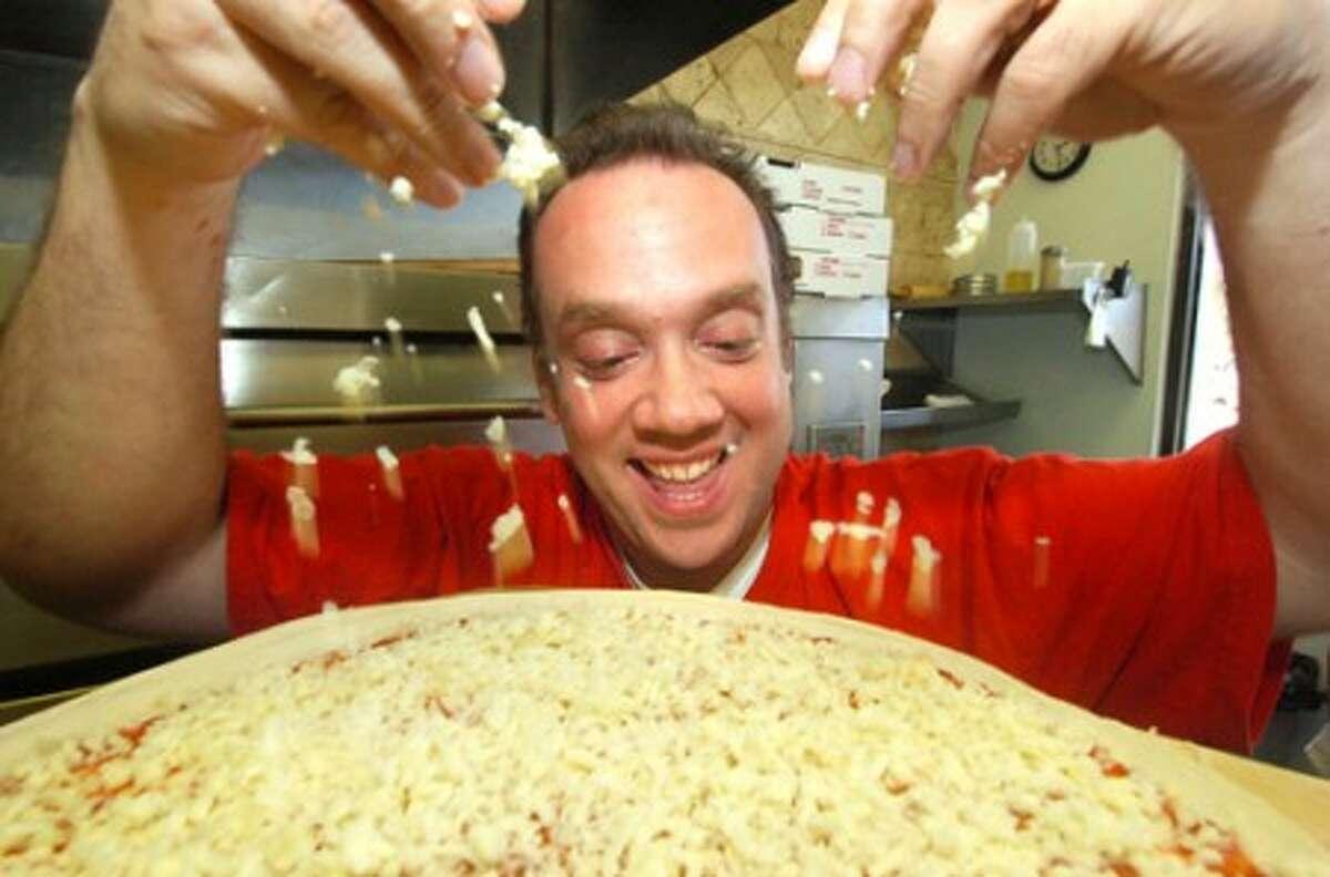 Photo/Alex von Kleydorff. Champion Pizza maker Bruno DiFabio, owner of Pinocchio Pizza gets the Mozzarella cheese on a world famous pie at his Wilton location.