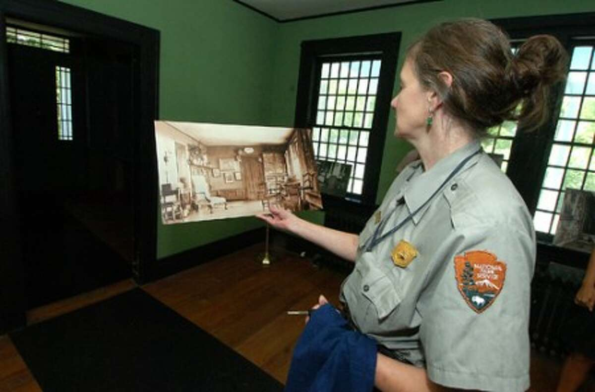 Photo/Alex von Kleydorff. Weir Farm NHS Superintendent Linda Cook holds a photo from circa 1900 of the living room at Weir House to compare to the current living room under renovation