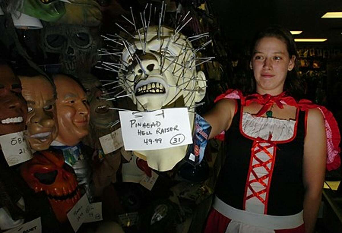 Sarah Agustyniak of Happy Daze costume shop in Norwalk displays one of the more popular masks for Hallowween this year at the store Saturday. Hour photo / Erik Trautmann