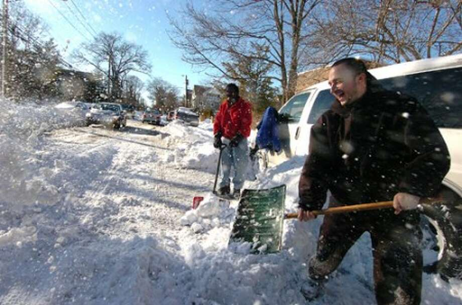Photo/Alex von Kleydorff. Wardell Clarke and Michael Putzig clear snow from a van for a friend in Glenbrook Stamford.
