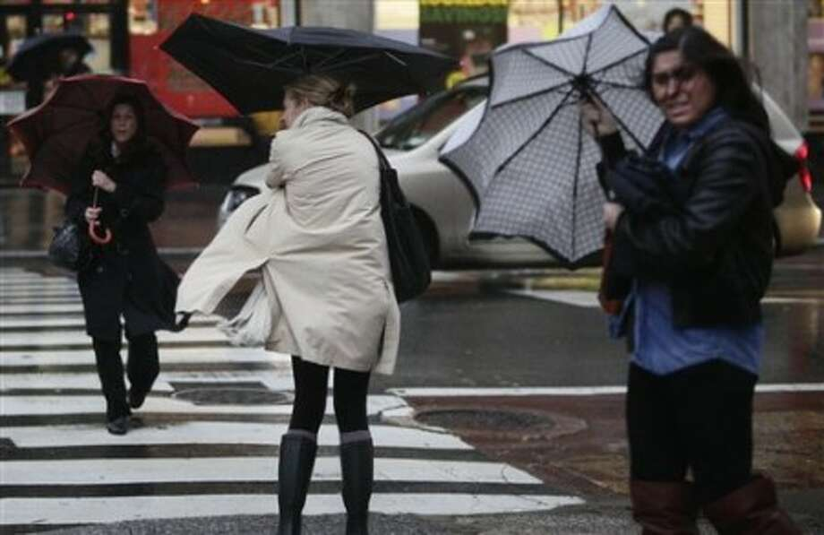 Pedestrians struggle with umbrellas during heavy rain and wind on Wednesday, Dec. 1, 2010, in New York. Flights were delayed up to five hours at the city''s three major airports as fast-moving storms and powerful, damaging winds battered large swaths of New York. (AP Photo/Bebeto Matthews)