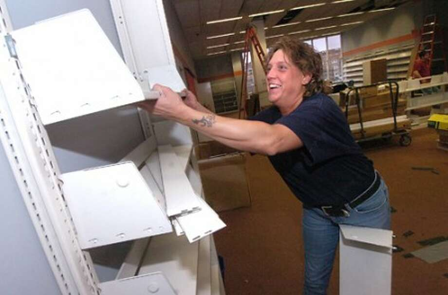 Photo/Alex von Kleydorff. Candi Bradtmuller a Mover/Library Relocation specialist, takes a set of shelves down off the wall on the third floor during remodeling at The Ferguson Library