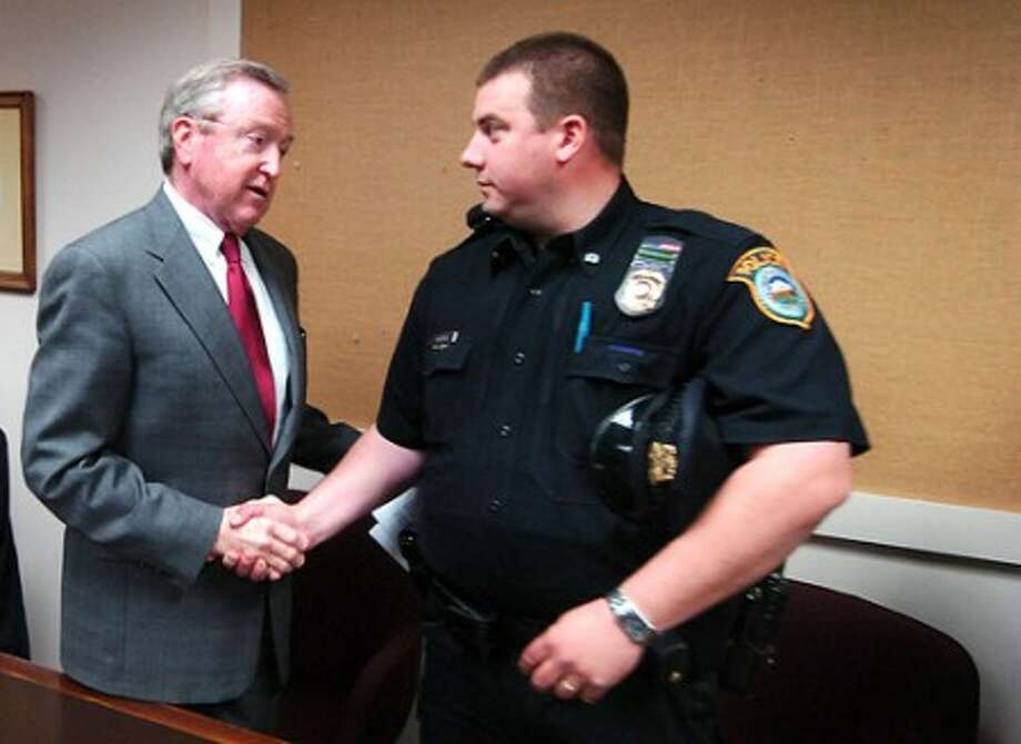 Photo/Alex von Kleydorff. Wilton First Selectman Bill Brennan shakes Wilton Police Union President, Officer David Hartman''s hand after Brennen read a statement about the town budget during a press conference Wednesday.