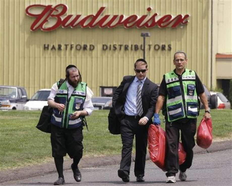Rabbi Mayer Berger, left, walks with a man carrying bags of blood-covered fabric outside the Hartford Distributors building, where a gunman killed eight and himself on Tuesday, in Manchester, Conn., Wednesday, Aug. 4, 2010. According to Rabbi Berger, he was there to retrieve all the body remains of Louis Felder Jr., who was expected to be buried later in the day. (AP Photo/Charles Krupa)