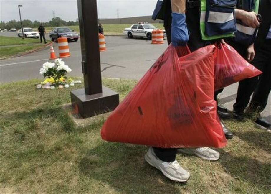 Bags of blood-covered fabric are carried from the Hartford Distributors building, where a gunman killed eight and himself on Tuesday, in Manchester, Conn., Wednesday, Aug. 4, 2010. (AP Photo/Charles Krupa)